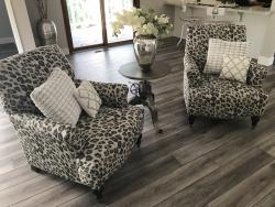 Grey leopard print arm chairs off of open kitchen over grey toned hardwood floors.