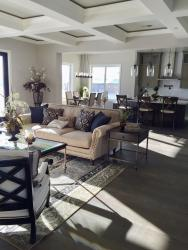 Staged living room with open floor plan into kitchen with island and bar stools. Medium-dark wood flooring.