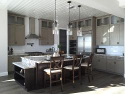 Staged kitchen with island, car stools, and pendant lighting.