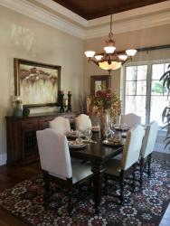 A beautiful staged dining room with dark wood finishes, upholstered wooden dining room chairs, and a traditional chandelier with bowl shaped sconces.