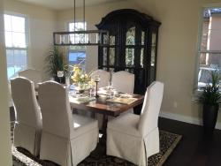 Staged dining room with white, covered chairs and a unique rectangular chandelier.